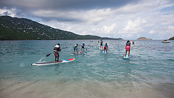 Six children ages 11-14 race into the water to practice stand up paddle-boarding in anticipation of Sunday's race.  Practicing for Paddle in the Park at Magen's Bay. St. Thomas, USVI.  24 October 2015. © Aisha-Zakiya Boyd