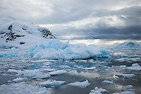 Jagged sea ice and icebergs with reflection on calm water, Antarctica. Icescapes and seascape photography wall art. Landscape fine art photography prints.