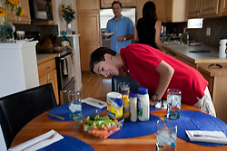 """Santiago Gonzalez, 13, sets the table for lunch at his home, Littleton, Colo., Aug. 28, 2011. Gonzalez is a full-time college student at the Colorado School of Mines, an engineering university. He wakes up at 5:30 a.m. every morning during the academic semester to develop iPad and iPhone applications in a programming language called Objective C, which he learned from a textbook when he was 9 years old. That textbook and 86 similar volumes including Applied Finite Mathematics, Infinity in Your Pocket, Programming in C++ and Dictionary of Physics, sit in a glass-fronted bookcase opposite his bed. """"Exceptionally gifted"""" is the commonly used phrase for kids as smart as Gonzalez."""