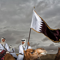 Desert riders with the Qatar National flag, Al Shahania, Qatar