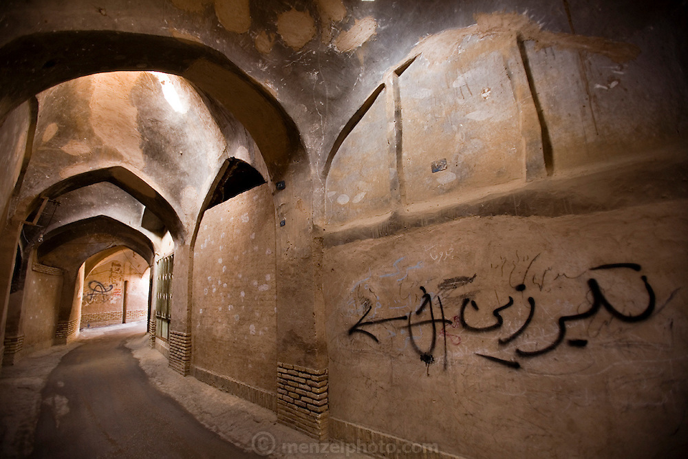 "Part of a labyrinth of covered streets and alleys that wind through the ancient mud brick city of Yazd, Iran. The grafitti on the wall on the right says ""battle-axe""."
