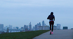 Primrose Hill, London, January 12th 2017. Dawn breaks over London, seen from Primrose Hill, as the South East of England braces itself for rain and possibly snow later in the day. PICTURED: A woman runs up to the summit of Primrose Hill.