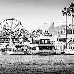Newport Beach Fun Zone panoramic photo in black and white. Panoramic photo ratio is 1:3 Picture includes Newport Harbor, Ferris Wheel, Tiki Boat, Balboa Car Ferry, and other popular attractions on Balboa Peninsula. Newport Beach is an affluent beach city in Orange County Southern California.