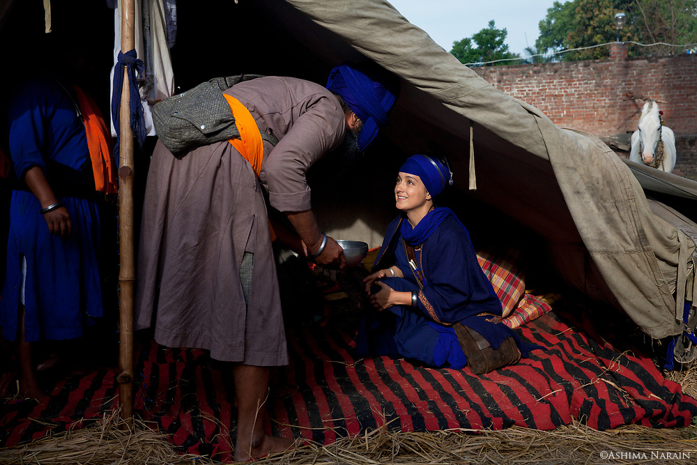 Harsangat Raj Kaur, an American Nihang, of Persian and Swedish origin is offered warm milk with saffron and almonds before the procession for the Sikh festival of Hola Mohalla begins.