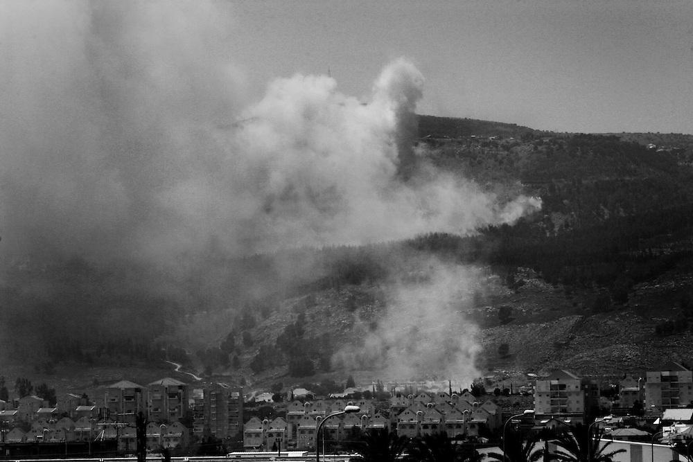 Hezbollah rockets land causing forest fires surrounding the northern Israeli town of Kiyrat Shmona. Aug 2006