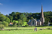 Couple walk their dog by Church of St Tysilio in Sellack, Herefordshire, England, United Kingdom