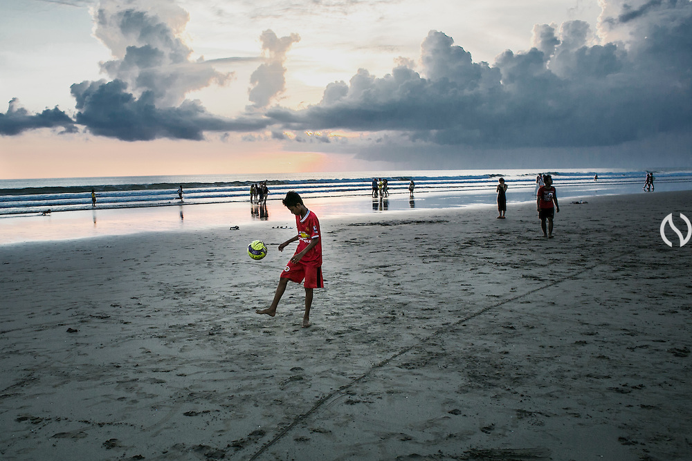 BALI, INDONESIA; MARCH 27, 2015: A boy juggles a ball at Seminyak Beach, Bali, Indonesia on Friday, March 27, 2015.