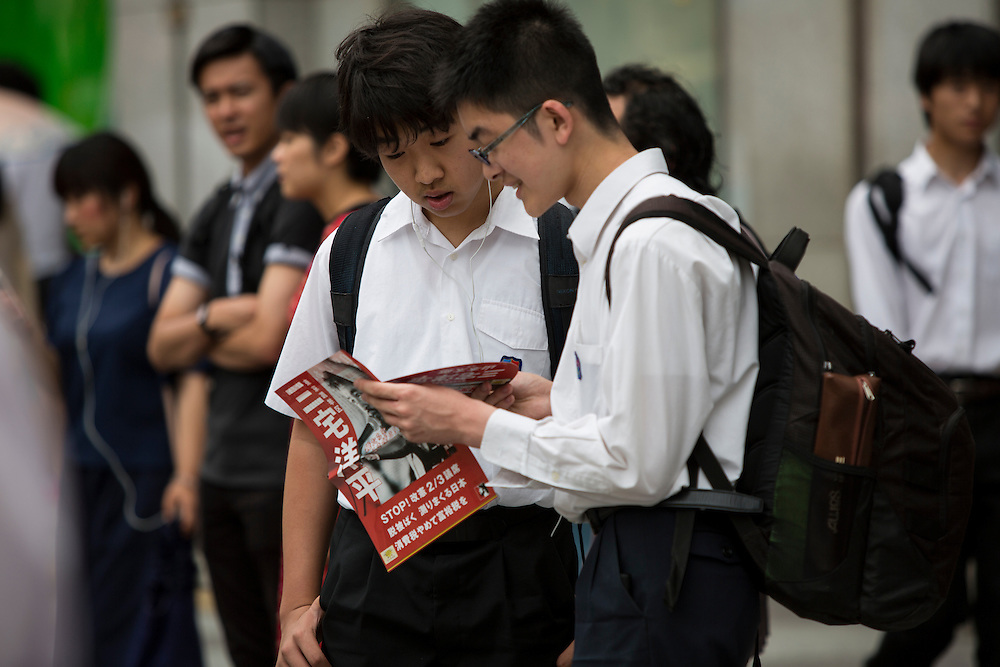 TOKYO, JAPAN - JULY 8 :  Students reads campaign leaflets in front of the station during the Upper House election campaign in Ikebukuro Station two days before the election,  Tokyo, Japan, on July 8, 2016. The July 10, 2016, Upper house election is the first nation-wide election in Japan after government law changes its voting age from 20 years old to 18 years old. (Photo by Richard Atrero de Guzman/NUR Photo)