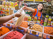 12 OCTOBER 2012 - NAKHON PATHOM, NAKHON PATHOM, THAILAND: A market vendor in the Nakhon Pathom market accepts payment for dried shrimp from a customer.   PHOTO BY JACK KURTZ