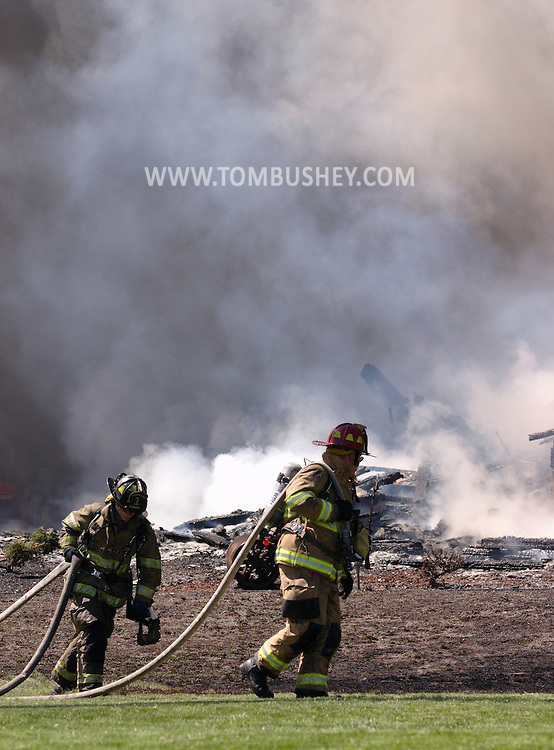 Goshen, N.Y. - Two firefighters pull hoses in front of the remains of a house destroyed by fire on April 29, 2006..©Tom Bushey