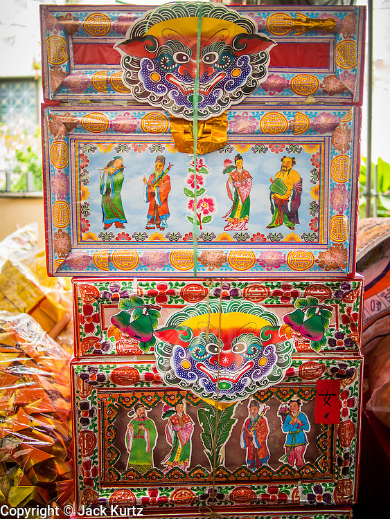 "26 AUGUST 2013 - BANGKOK, THAILAND: Hungry Ghost coffins people donate to the Poh Teck Tung Foundation for Hungry Ghost Month in Bangkok. Poh Teck Tung operates hospitals and schools and provides assistance to the poor in Thailand. The seventh lunar month (August - September in 2013) is when the Chinese community believes that hell's gate will open to allow spirits to roam freely in the human world for a month. Many households and temples will hold prayer ceremonies throughout the month-long Hungry Ghost Festival (Phor Thor) to appease the spirits. During the festival, believers will also worship the Tai Su Yeah (King of Hades) in the form of paper effigies which will be ""sent back"" to hell after the effigies are burnt.    PHOTO BY JACK KURTZ"