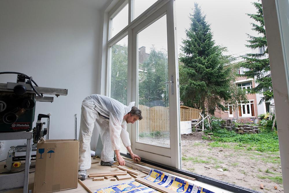 Nederland. Rotterdam, 26 juli 2007.<br /> Pim Bangert (spelling checken svp) ruimt houten planken op  Hij heeft in de wijk Spangen goedkoop een casco huis gekocht. Wijkverbetering. Repo Gerard Reijn.<br /> Foto Martijn Beekman <br /> NIET VOOR TROUW, AD, TELEGRAAF, NRC EN HET PAROOL