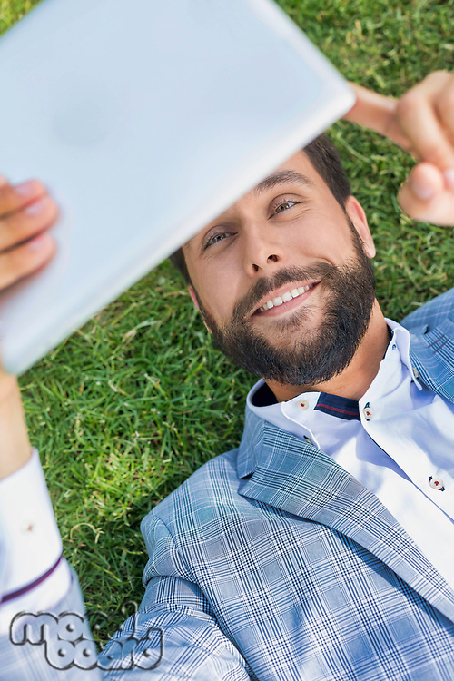 Young attractive businessman using digital tablet while lying on the grass