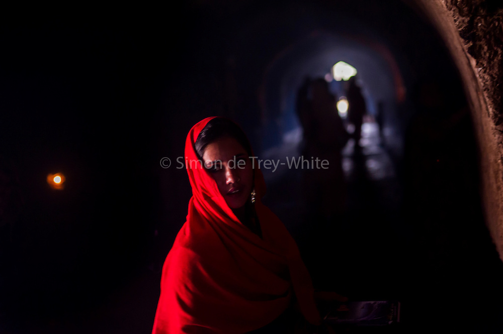 10th December 2015, New Delhi, India. A woman in the ruins of Feroz Shah Kotla in New Delhi, India on the 10th December 2015<br /> <br /> PHOTOGRAPH BY AND COPYRIGHT OF SIMON DE TREY-WHITE a photographer in delhi<br /> + 91 98103 99809. Email: simon@simondetreywhite.com<br /> <br /> People have been coming to Firoz Shah Kotla to pray to and leave written notes and offerings for Djinns in the hopes of getting wishes granted since the late 1970's. Jinn, jann or djinn are supernatural creatures in Islamic mythology as well as pre-Islamic Arabian mythology. They are mentioned frequently in the Quran  and other Islamic texts and inhabit an unseen world called Djinnestan. In Islamic theology jinn are said to be creatures with free will, made from smokeless fire by Allah as humans were made of clay, among other things. According to the Quran, jinn have free will, and Iblīs abused this freedom in front of Allah by refusing to bow to Adam when Allah ordered angels and jinn to do so. For disobeying Allah, Iblīs was expelled from Paradise and called &quot;Shayṭān&quot; (Satan).They are usually invisible to humans, but humans do appear clearly to jinn, as they can possess them. Like humans, jinn will also be judged on the Day of Judgment and will be sent to Paradise or Hell according to their deeds. Feroz Shah Tughlaq (r. 1351&ndash;88), the Sultan of Delhi, established the fortified city of Ferozabad in 1354, as the new capital of the Delhi Sultanate, and included in it the site of the present Feroz Shah Kotla. Kotla literally means fortress or citadel.
