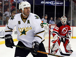 November 28, 2007; Newark, NJ, USA;  Dallas Stars center Mike Modano (9) skates while New Jersey Devils goalie Martin Brodeur (30) watches the puck during the third period at the Prudential Center in Newark, NJ.  The Devils rallied to beat the Stars 4-2.