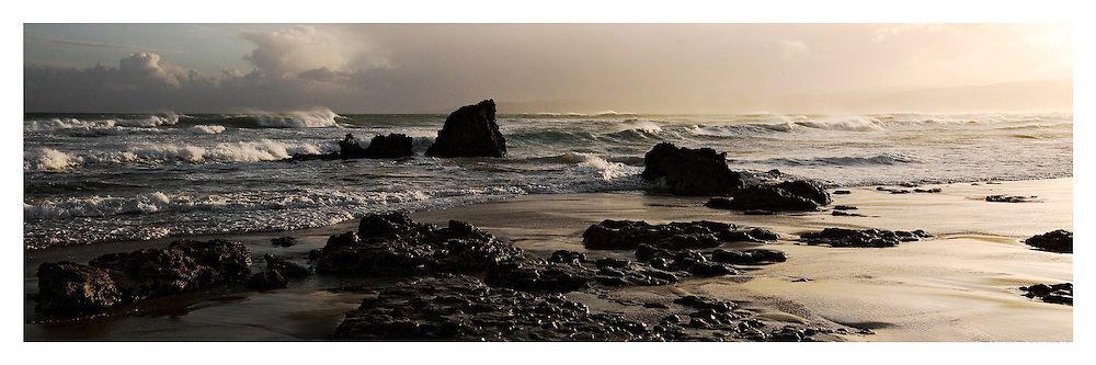 Waves breaking over rocks in evening light at Aireys Inlet