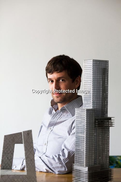 BEIJING, AUG.5, 2012 : Stararchitekt Ole Scheeren sitzt zwischen  zwei Modellen seiner Bauten in seinem Buero in Peking.