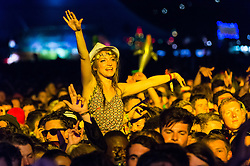 © Licensed to London News Pictures. 05/09/2014. Isle of Wight, UK. Female festival goers at Bestival 2014 Day 2 Friday watch MainStage headline act Outkast perform from the tops of their friends shoulders.  This weekend's headliners include Chic featuring Nile Rodgers, Foals and Outcast.   Bestival is a four-day music festival held at the Robin Hill country park on the Isle of Wight, England. It has been held annually in late summer since 2004.    Photo credit : Richard Isaac/LNP
