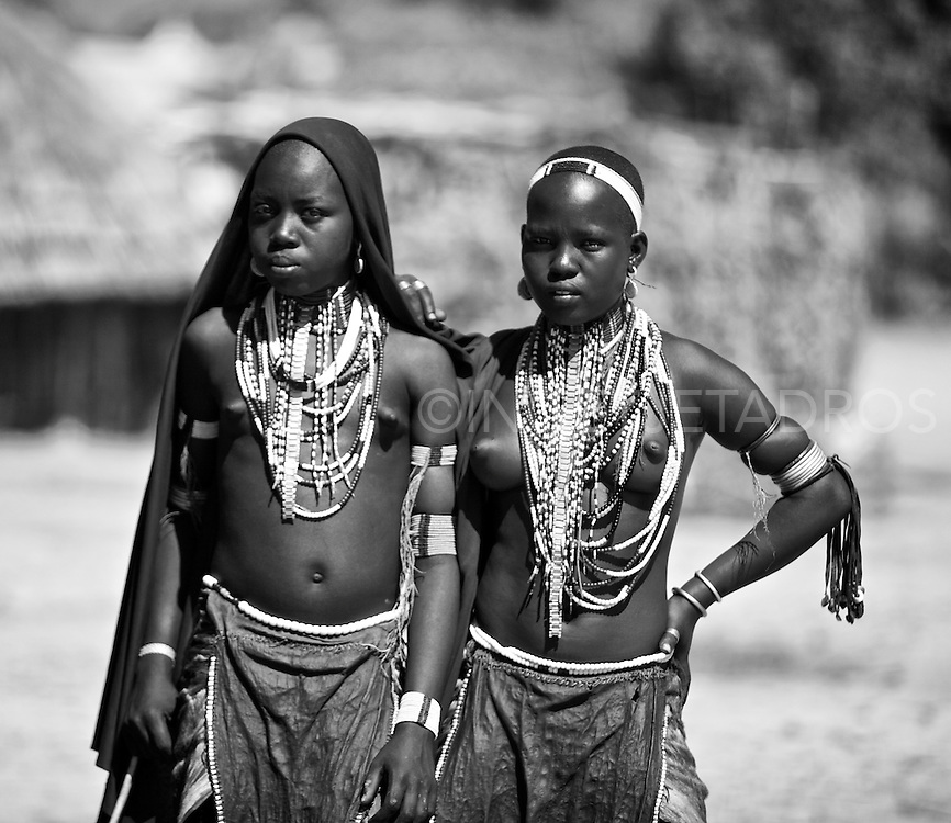 Young Arbore girls, in traditional outfit. These young girls are so beautiful. They wear many necklaces in bright colours and lovely earrings.This is a very exotic and a small tribe living in the Weyto Valley Desert living in a very harsh physical enviroment. The Arbore women generally wear a large black cloth to cover their heads. They perform many ritual-like dances while singing. They believe that dancing and singing with eliminate negative energies and give positive energy that will bring good-luck. The Arbore measure their wealth by the number of cattle they own..<br /> <br /> This is a very exotic and a small tribe living in the Weyto Valley Desert living in a very harsh physical enviroment. The Arbore women generally wear a large black cloth to cover their heads. They perform many ritual-like dances while singing. They believe that dancing and singing with eliminate negative energies and give positive energy that will bring good-luck. The Arbore measure their wealth by the number of cattle they own..