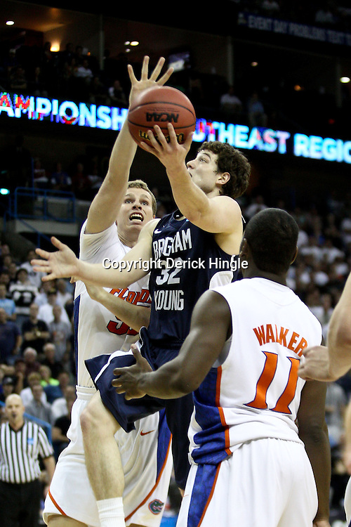 Mar 24, 2011; New Orleans, LA; Brigham Young Cougars guard Jimmer Fredette (32) shoots over Florida Gators forward Erik Murphy (33) during the first half of the semifinals of the southeast regional of the 2011 NCAA men's basketball tournament at New Orleans Arena.  Mandatory Credit: Derick E. Hingle