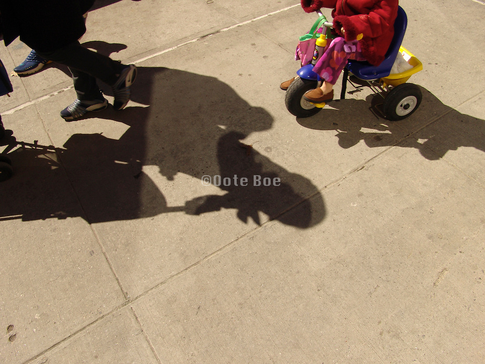 shadow of mother with stroller and child on three wheeler.