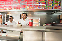 Two mid adult men working in fast food shop