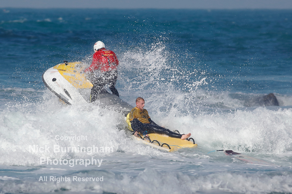 Fistral Beach, Newquay, Cornwall, UK. 13th October, 2017. Surfers take part in Day 1 heats of the British University and College Sports Surfing Competition. A surfer is helped by the RNLI away from the rocks on the north side of the beach.