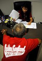 NEW ORLEANS, LA- June 22:  Chinh Nguyen meets with a volunteer to receive assitance... Vietnamese affected by the Gulf oil spill because of their work in the fishing industry, wait on an early morning line at Mary Queen of Vietnam Catholic Church to receive financial assistance from Catholic Community Services, in New Orleans, Louisiana, Tuesday June 22, 2010.  (Melina Mara/The Washington Post)