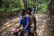 Maniq men leave for work on motorbikes scrambling along the muddy dirt tracks. <br /> <br /> Evidence suggests that the Maniq, a Negrito tribe of hunters and gatherers, have inhabited the Malay Peninsula for around 25,000 years. Today a population of approximately 350 maniq remain, marooned on a forest covered mountain range in Southern Thailand. Whilst some have left their traditional life forming small villages, the majority still live the way they have for millennia, moving around the forest following food sources. <br /> <br /> Quiet and reclusive they are little known even in Thailand itself but due to rapid deforestation they are finding it harder to survive on the forest alone and are slowly being forced to move to its peripheries closer to Thai communities.