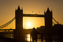© Licensed to London News Pictures. 02/01/2017. LONDON, UK.  A golden sunrise behind Tower Bridge on the River Thames in London this morning during cold and clear weather following heavy rain yesterday.  Photo credit: Vickie Flores/LNP