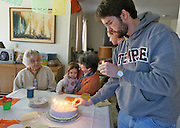 Father prepares birthday cake for daughter's birthday and elderly Aunt as grandmother holds child.