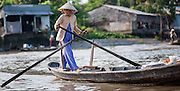 Old woman paddling on a boat on Mekong Delta (Vietnam)