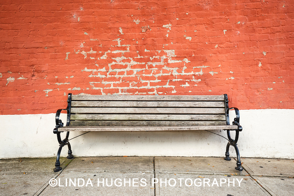 Brick background with old wooden bench
