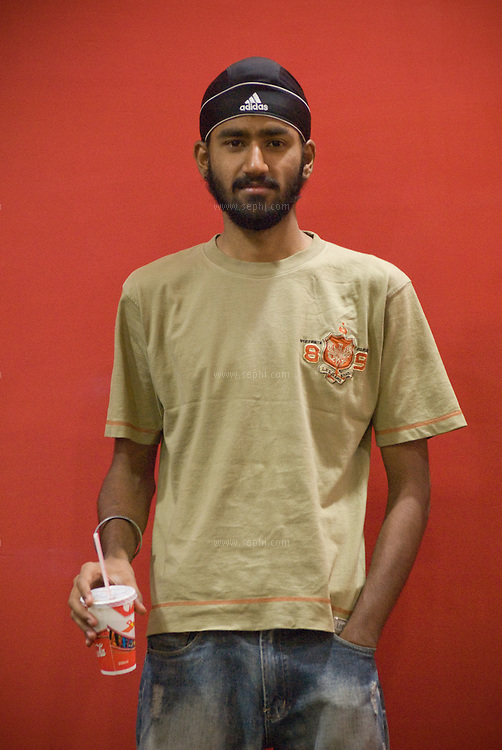 Sumit (20),  a young Sikh guy wearing an Adidas turban and holding a cup of Coke at the cafeteria of the Wave Cinema complex at the West End mall in Moradbad, UP