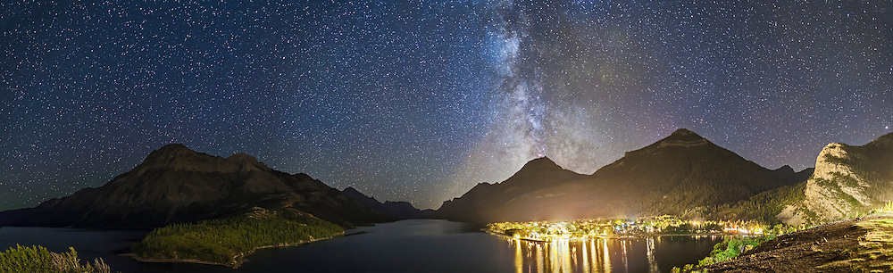 A 5-section panorama of Waterton Lakes National Park, around Upper Waterton Lake, looking south from the promontory site of the Prince of Wales Hotel, overlooking the townsite on a dark moonless night, August 31, 2013. Each frame is a 30  second exposure with the 24mm lens at f/2.5 and Canon 5D MkII at ISO 2500. Stitched in Photoshop. If there was a case for making Waterton a Dark Sky Preserve, this is it. Unshielded lights illuminate the entire valley and make it impossible to see the stars and Milky Way from the town and Hotel site.