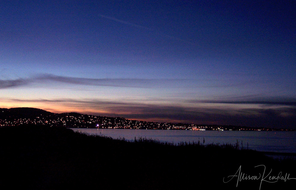 The last colors of sunset fade from the sky as the city lights of Monterey appear along the waterfront.