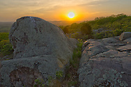 The sun sets in between two boulders. The boulders are part of a glade, which is a rocky, treeless area commonly found in the Ozark Mountains of Missouri.<br /> <br /> Date Taken: May 5, 2014