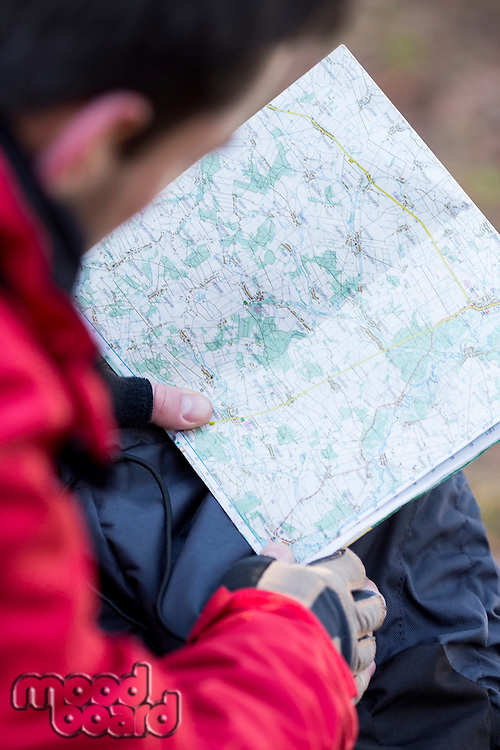 Cropped image of male hiker reading map