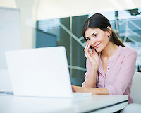 Beautiful young businesswoman using mobile phone while looking at laptop in office