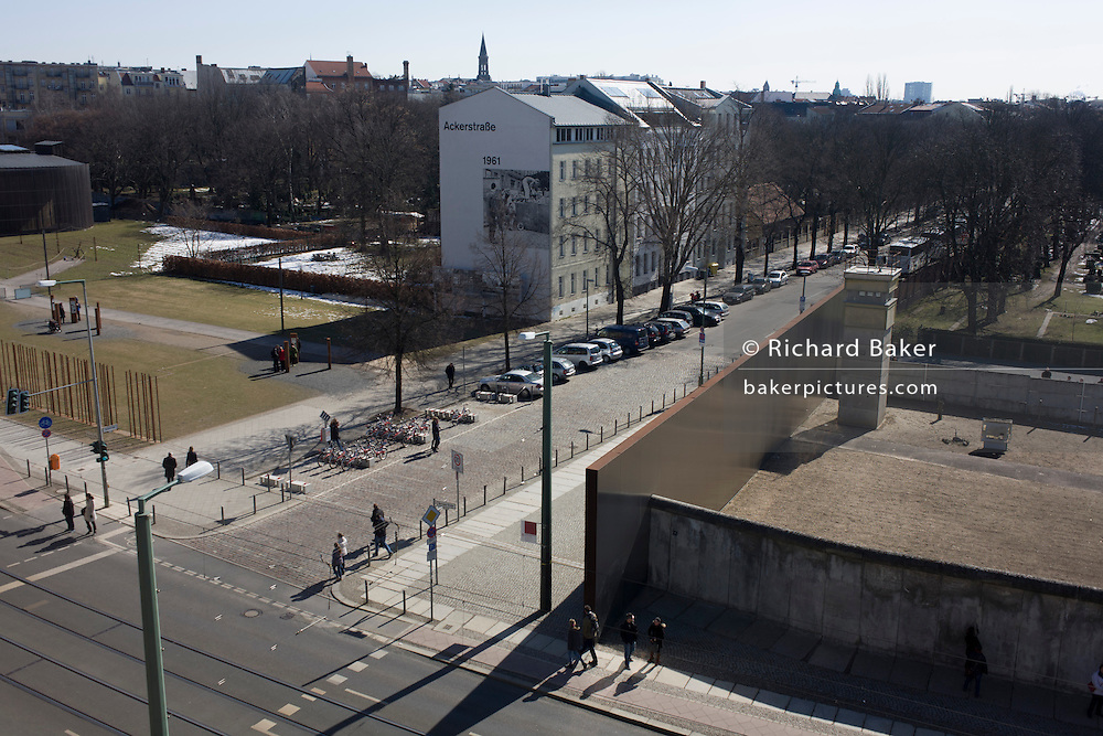 "Aerial landscape of Bernauer Strasse, showing a section of preserved Berlin wall where East Germans were killed while trying to cross the former border between Communist East and West Berlin during the Cold War. The Berlin Wall was a barrier constructed by the German Democratic Republic (GDR, East Germany) starting on 13 August 1961, that completely cut off (by land) West Berlin from surrounding East Germany and from East Berlin. The Eastern Bloc claimed that the wall was erected to protect its population from fascist elements conspiring to prevent the ""will of the people"" in building a socialist state in East Germany. In practice, the Wall served to prevent the massive emigration and defection that marked Germany and the communist Eastern Bloc during the post-World War II period."
