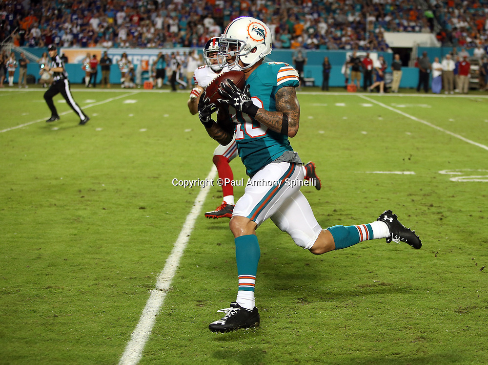 Miami Dolphins wide receiver Kenny Stills (10) runs for the end zone as he catches a 47 yard third quarter touchdown pass good for a 24-17 Dolphins lead while being chased by New York Giants defensive back Craig Dahl (43) during the NFL week 14 regular season football game against the New York Giants on Monday, Dec. 14, 2015 in Miami Gardens, Fla. The Giants won the game 31-24. (©Paul Anthony Spinelli)