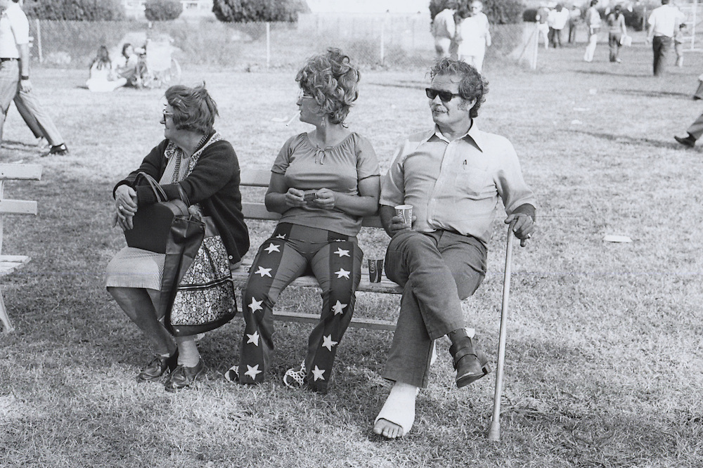 Spectators at the third Louisiana Jazz and Heritage Festival in 1972 sit on bench and listen to music.