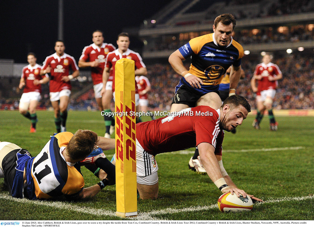 11 June 2013; Alex Cuthbert, British & Irish Lions, goes over to score a try despite the tackle from Tom Cox, Combined Country. British & Irish Lions Tour 2013, Combined Country v British & Irish Lions, Hunter Stadium, Newcastle, NSW, Australia. Picture credit: Stephen McCarthy / SPORTSFILE