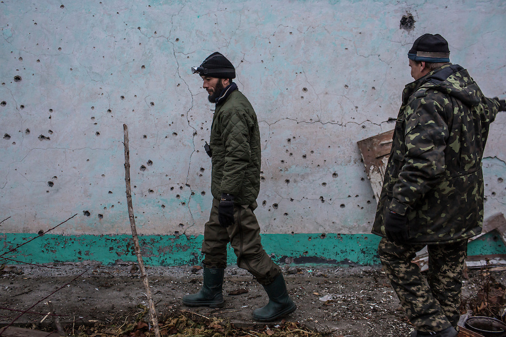 PIKSY, UKRAINE - NOVEMBER 19, 2014: Members of the Dnipro-1 brigade, a pro-Ukraine militia, walk past shrapnel damage outside the house where they live with other brigade members in Pisky, Ukraine. The village of Pisky is the scene of much of the front-line fighting over the Donetsk airport. CREDIT: Brendan Hoffman for The New York Times