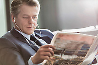 Mature attractive businessman reading newspaper while waiting and listening to music in airport