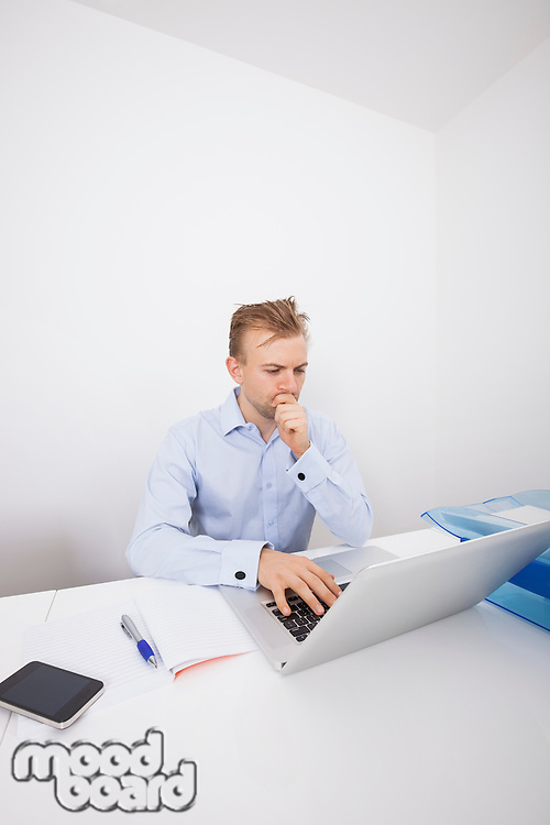 Concentrated businessman using laptop at desk in office
