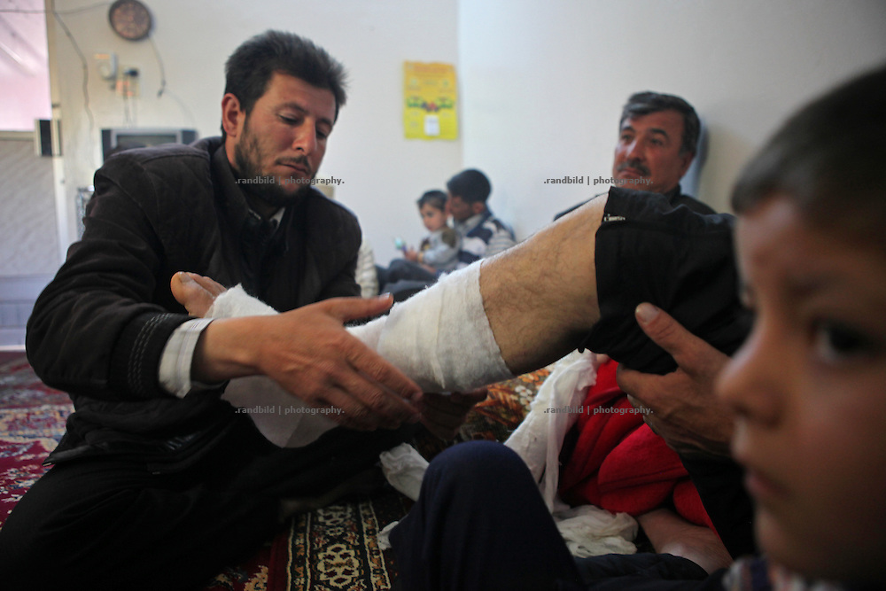 A brother of a wounded man wraps his leg in a bandage. Courine was been attacked by ground troops on February 22, 2012 (see archive images). aftermath air force helicopters shot  rockets several times into the 7000 inhabitants counting village south of Idlib city. Courine ist still a stronghold of opposition.
