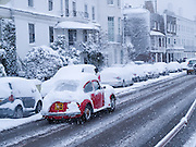 A red car covered in snow driving through Barnes