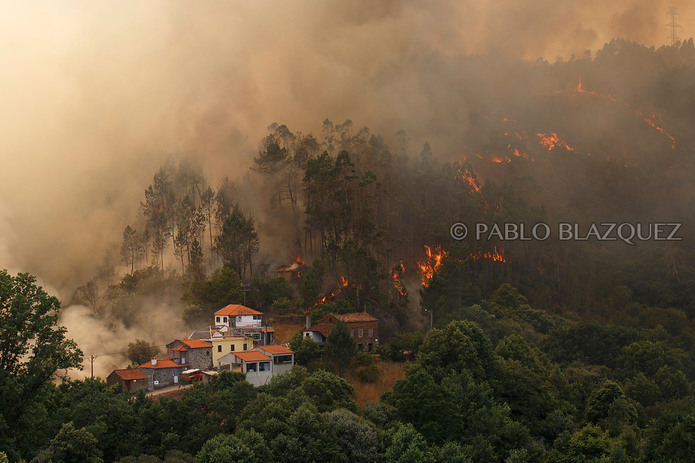 LEIRIA, PORTUGAL - JUNE 18:  A house burns as a wildfire approaches to Mega Fundeira village after a wildfire took dozens of lives on June 20, 2017 near Picha, in Leiria district, Portugal. On Saturday night, a forest fire became uncontrollable in the Leiria district, killing at least 62 people and leaving many injured. Some of the victims died inside their cars as they tried to flee the area.  (Photo by Pablo Blazquez Dominguez/Getty Images)