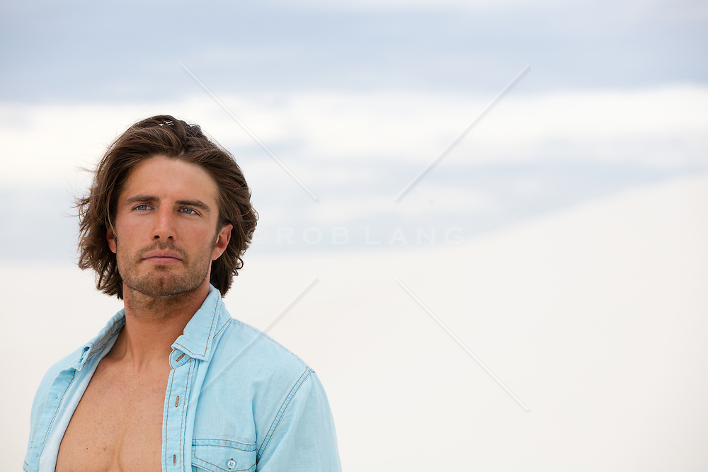 portrait of a handsome man with long brown hair and blue eyes outdoors
